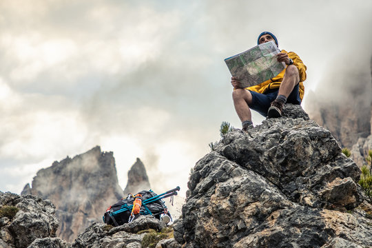 Young man hiker sitting on stone mountain reading map, with cloudy sky and fog. Yellow jacket, backpack, black beard and beanie. Traveling dolomites, Italy.