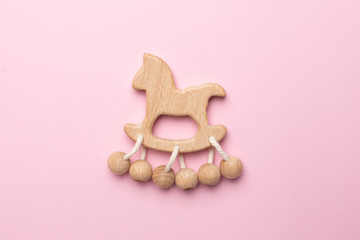 Baby wooden rattle and toy on pink background isolated