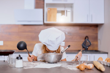 little baker girl interested in baking and cooking, look at dough in bowl, wearing apron and white cap for cooking, holding scapulas isolated in kitchen