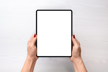 Tablet mockup. Girl holding tablet in vertical position abowe white desk. Flat lay, top view
