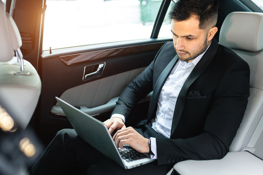handsome confident businessman typing on laptop, busy young caucasian man sit in luxurious car wearing tuxedo