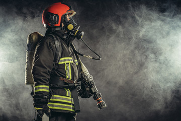 strong firefighter in protective suit and helmet use special equipment for preventing fire and save people and animals from fire