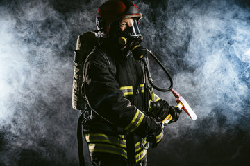 strong confident fireman saving and protecting from fire, wearing protective helmet and suit, working in fire station