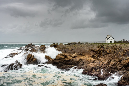 Storm on the coast in Brittany. The waves are smashing on the rocks under a rainy sky. A small white house stands in the wind.