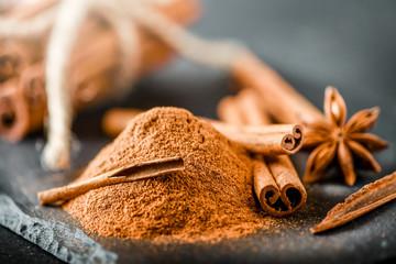 Heap of cinnamon powder on dark stone table. Cinnamons sticks in bunch at black board.