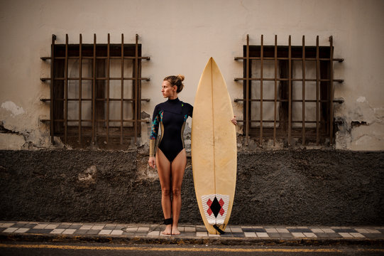 Fit girl in the black diving suit standing on the street near a yellow surfing board