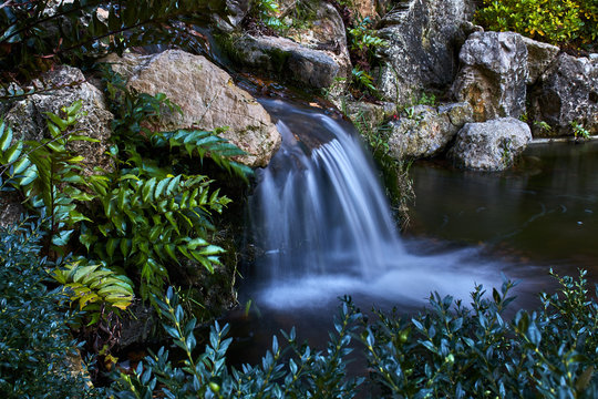 Small waterfall between rocks and plants