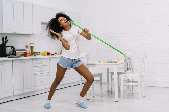 Happy emotional housewife dancing in kitchen. Beautiful African American woman holding mop and singing song, having fun at home. Portrait of young cute female cleaner at work. Housework concept