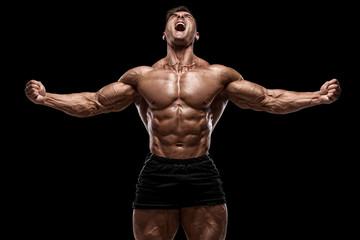 Muscular man showing muscles isolated on the black background. Strong male naked torso abs