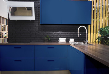 Modern kitchen interior with black brick walls, wooden countertops with a built in sink and a cooker.