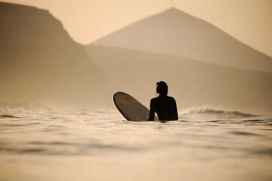 Rear view woman in the black diving suit sitting on the surfing board in the sunset time