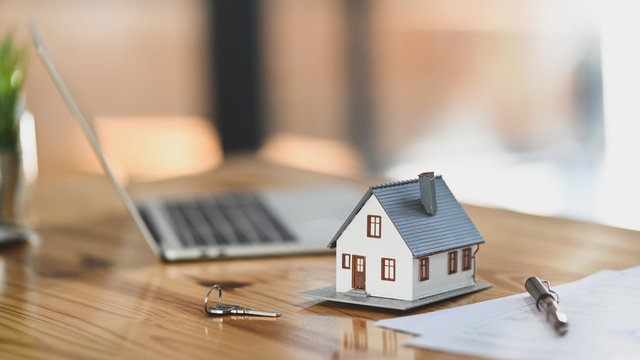 House model on sale keys on the rental agreement or the buy home contracts with the estate property background.