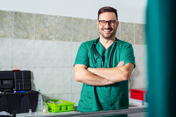 Portrait of veterinarian standing crossed arms at veterinary clinic.