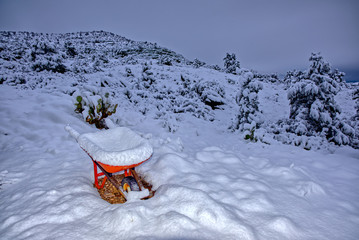 An old wheel barrow sitting on the slope of Sullivan Butte in Chino Valley AZ covered in snow from an overnight winter storm.