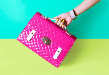 Wall Mural - Colourful pink handbag with girl's hand. Yellow manicured finger nails.