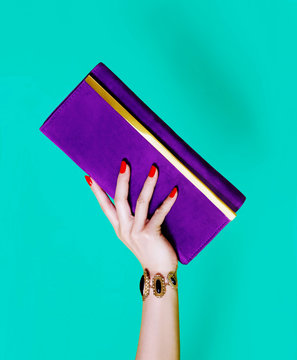 Purple purse wallet with beautiful woman hand isolated on green background