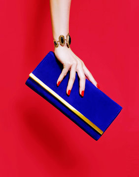 Beautiful hand with red manicure holding a purse wallet on red background