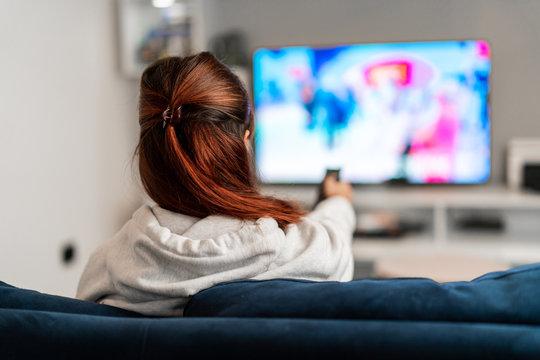 Girl watching tv programs on the sofa
