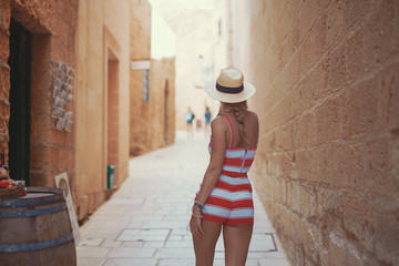 Young woman in hat walking on Mediterranean street