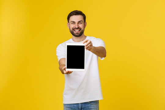 Creative young programmer presents with a smile on his face display a tablet.