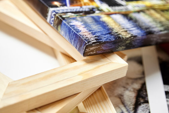 Print photography on canvas. Colorful photo, stack of wooden stretcher bars. Stretched photo canvas with gallery wrapping method, closeup, side view