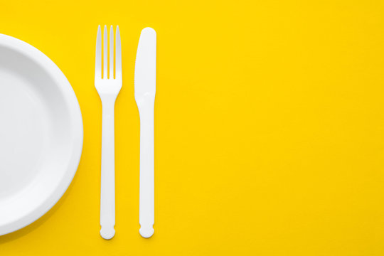 Plastic white fork, knife and plate on yellow background. Cooking utensil. Top view. Minimalist Style. Copy, empty space for text