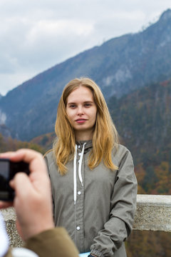 Blonde hipster girl posing in front of smart phone in men hands on the background of mountains. Autumn in Montenegro, partial defocus.