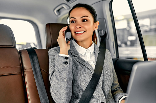 Beautiful young business woman in the car talking on phone and works on a laptop.