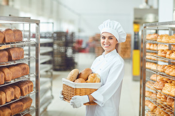 Zelfklevend Fotobehang Bakkerij A baker woman holding a basket of baked in her hands at the bakery