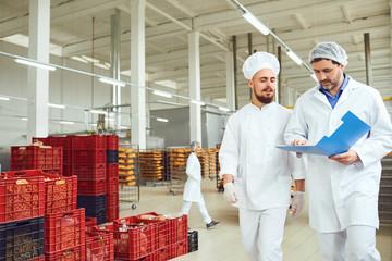 Keuken foto achterwand Bakkerij The technologist and baker speak in a bread factory.