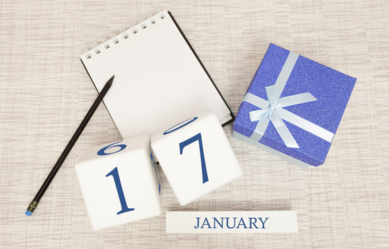 Calendar with trendy blue text and numbers for January 17 and a gift in a box.