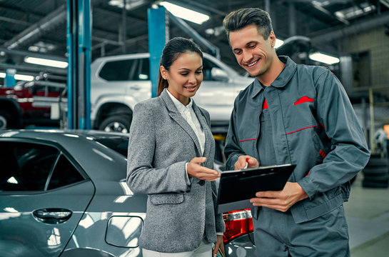 Beautiful businesswoman and auto service mechanic are discussing the work and signing documents. Car repair and maintenance.