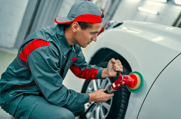 Auto mechanic buffing car autobody. Car repair and maintenance.