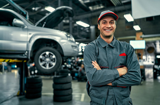 Handsome auto service mechanic in uniform is standing on the background of car with open hood, smiling and looking at camera. Car repair and maintenance.
