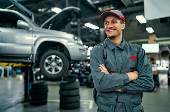 Handsome auto service mechanic in uniform is standing on the background of car with open hood, smiling and looking away. Car repair and maintenance.