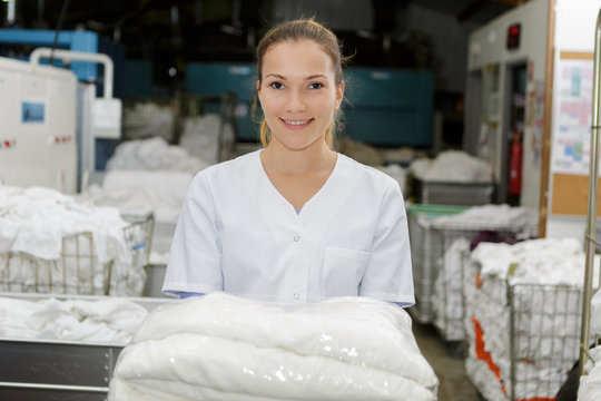 laundry worker holding stack of towels