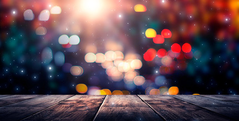 Fotomurales - Wooden table, blurred bokeh background background. Neon light, night view, close-up. The general background of the interior, a dark background.