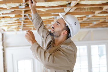 Obraz male builder working on ceiling joists - fototapety do salonu