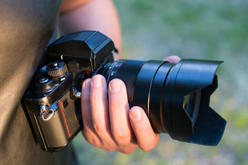 Closeup of a black camera holding by man's hand with natrural blackground in sunny day.