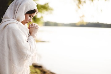Shallow focus shot of a female wearing s biblical gown and praying while her eyes are closed