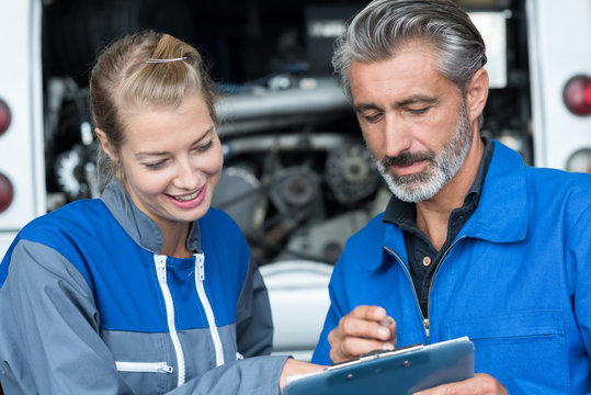 man and woman auto mechanics in a car workshop