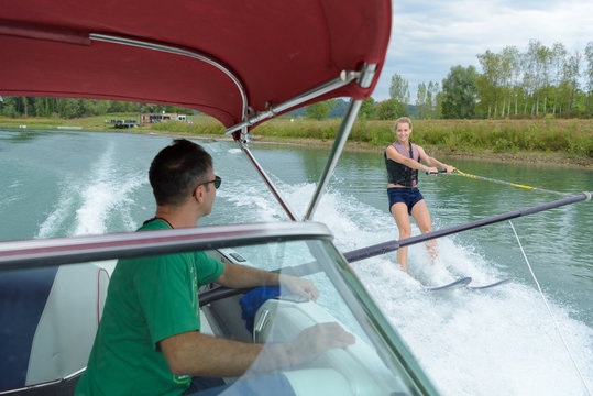 woman water skiing holding bar parallel to boat