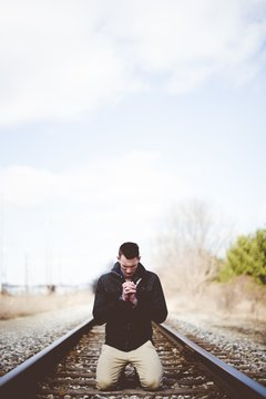 Vertical shot of a male on his knees on train tracks and praying while his eyes are closed