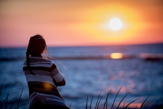 Shallow focus shot from behind of a female looking at the sea at sunset