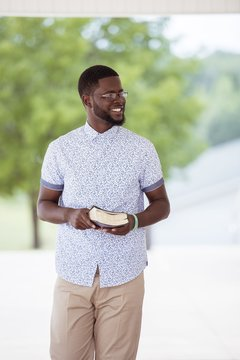 Vertical shot of a male walking while holding the bible and smiling