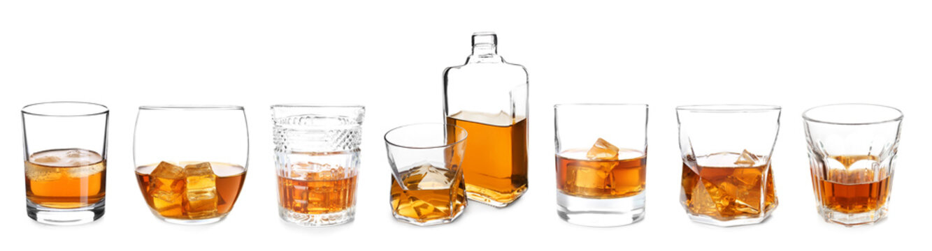 Bottle and glasses of whiskey on white background