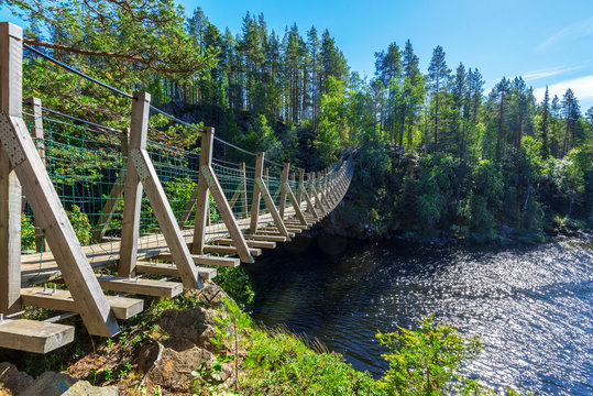 Suspended bridge through the water course between Jyravanjarvi and Ala-Juumajarvi lakes in Oulanka National Park in Finland. Pieni Karhunkierros Trail.