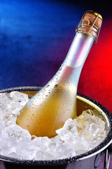 Bottle of sparkiling wine in bucket with crushed ice