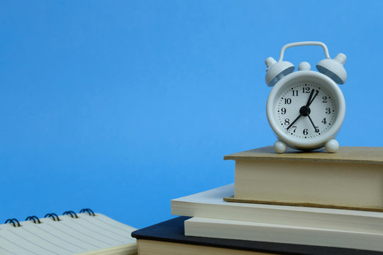 Office workload concept - stack of book with clock on the top