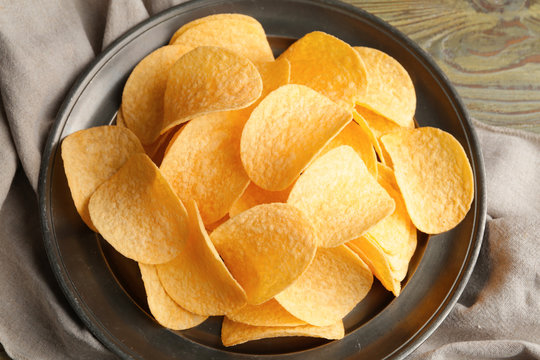 Plate with tasty potato chips on table